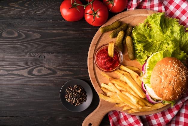 Composición de deliciosas hamburguesas y papas fritas con espacio de copia