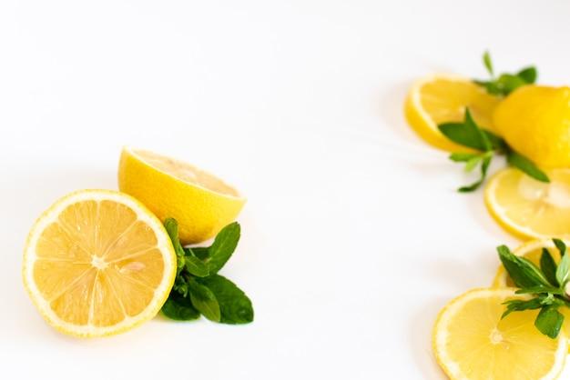 Composición de deliciosos cítricos y hojas verdes sobre blanco