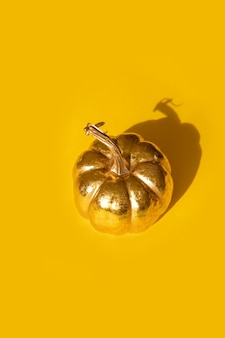 Composición del día de acción de gracias de otoño otoño con calabaza dorada decorativa sobre fondo amarillo