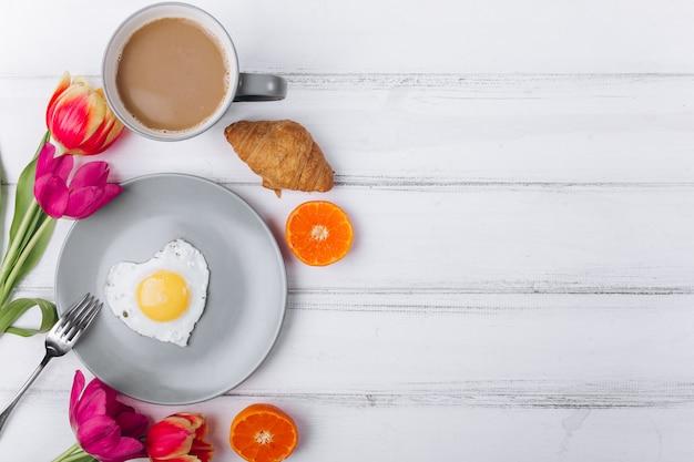 Composición del día de la madre. desayuno con los tulipanes en el fondo blanco.