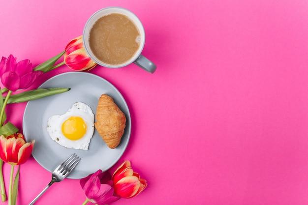 Composición del día de la madre. desayuno con los tulipanes en fondo rosado.