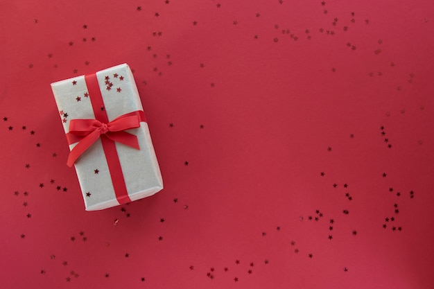 Composición del día de navidad o san valentín con espacio de copia. caja de regalo con adornos de cinta roja y confeti sobre fondo de colores de papel pastel.