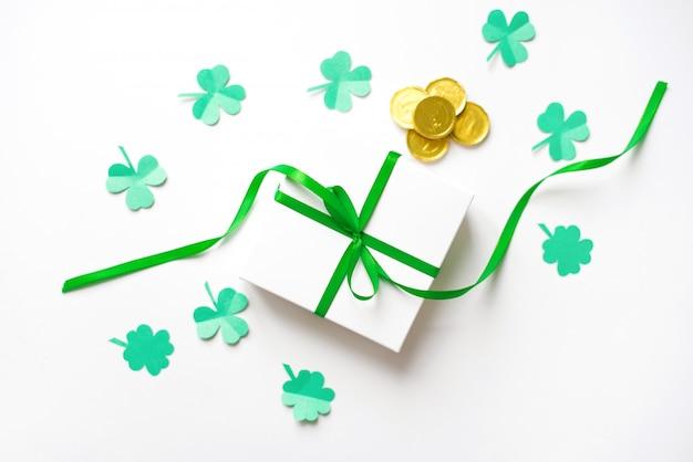 Composición para el día de san patricio. caja de regalo blanca con un lazo de satén verde, trébol y monedas de oro de juguete sobre un fondo blanco.