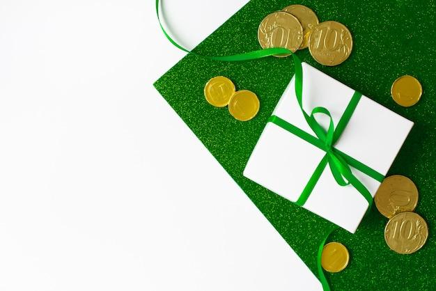 Composición del día de san patricio. caja de regalo blanca con lazo verde y monedas de oro sobre un fondo verde brillante y blanco