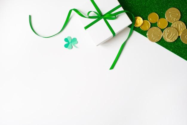 Composición del día de san patricio. caja de regalo blanca con un lazo verde, un trébol de papel y monedas de oro sobre un fondo verde brillante y blanco