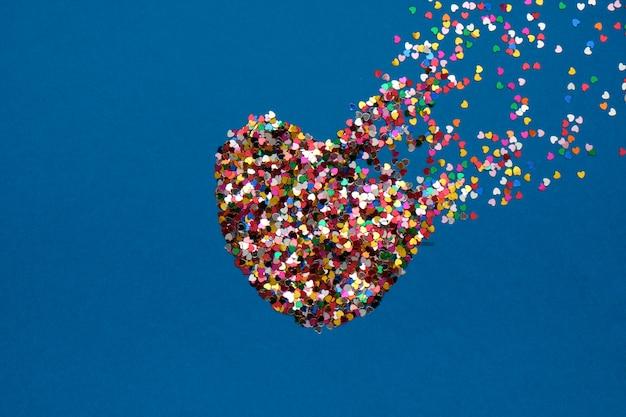 Composición del día de san valentín con corazón roto hecho de confeti sobre fondo azul clásico