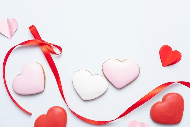 Composición del día de san valentín. galletas rojas dulces en forma de corazones enamorados del arco. plantilla, fondo. vista superior. endecha plana. copia espacio