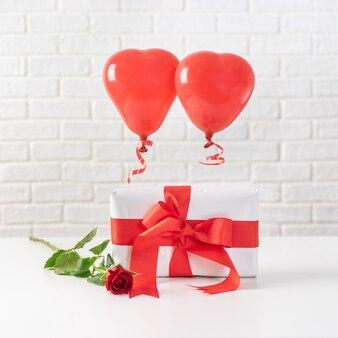 Composición del día de san valentín con globos rojos y caja de regalo