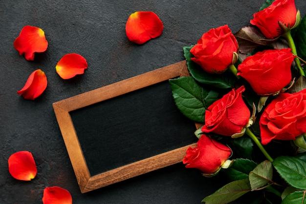 Composición del día de san valentín con rosas y marco de pizarra