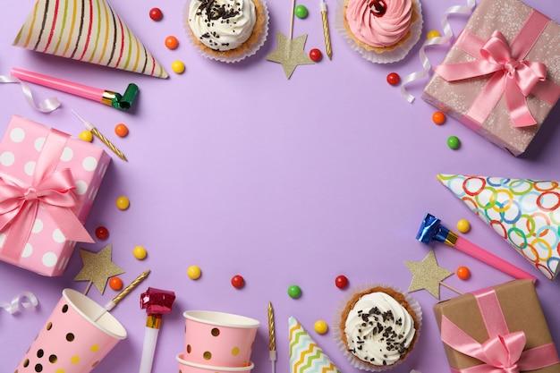 Composición con diferentes accesorios de cumpleaños sobre fondo violeta, espacio para texto