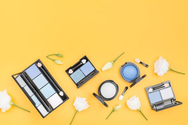 Composición de diferentes cosméticos con copia espacio sobre fondo amarillo.