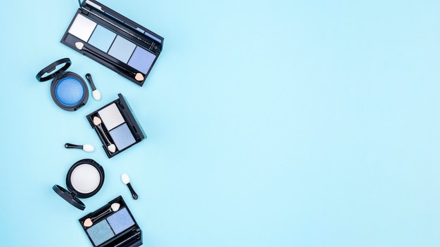 Composición de diferentes cosméticos con copia espacio sobre fondo azul.