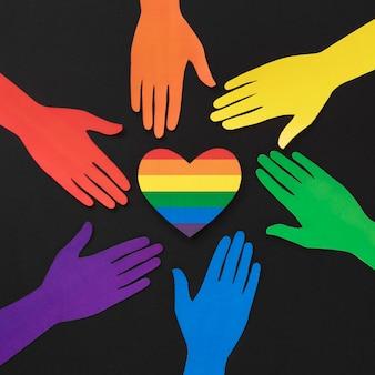 Composición de diversidad de manos de papel de diferentes colores con corazón de arco iris