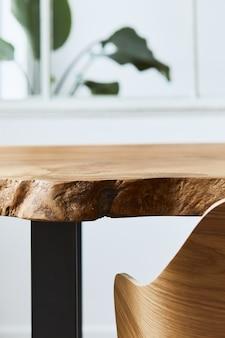 Composición elegante y acogedora de mesa de madera de roble artesanal con sillas, planta y piso moderno en el hermoso interior de la casa de diseño. plantilla.
