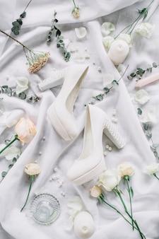 Composición elegante de boda con zapatos de tacón alto, ramas de eucalipto, flores rosas en textil blanco