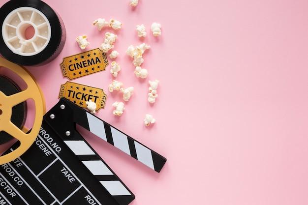 Composición de elementos de cine sobre fondo rosa con espacio de copia