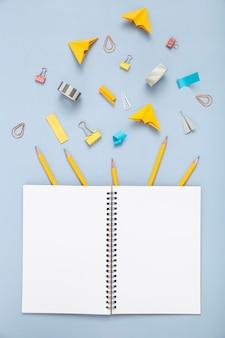 Composición de elementos de escritorio con cuaderno vacío abierto