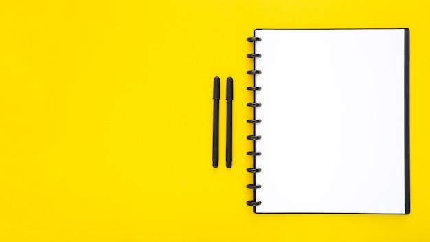 Composición de elementos de escritorio sobre fondo amarillo.