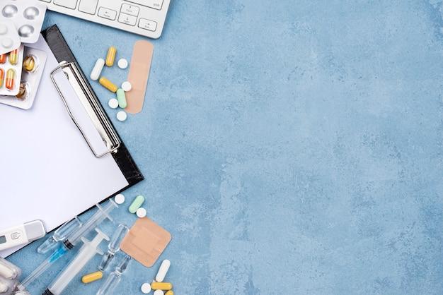 Composición de elementos médicos sobre fondo de cemento azul con espacio de copia