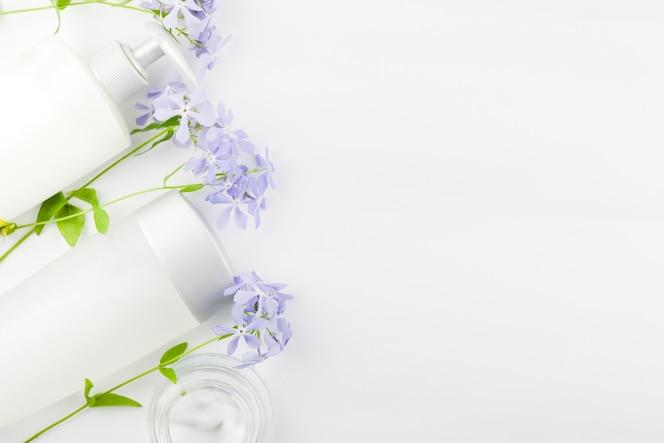 Composición en colores pastel de cosméticos y flores