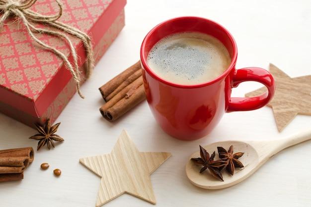 Composición de la época navideña con taza roja de café caliente con especias