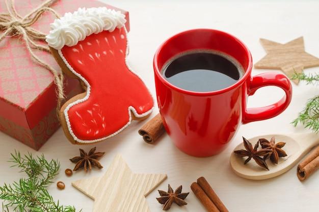 Composición de la época navideña con taza roja de café y galleta de jengibre