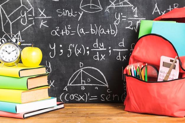Composición escolar con libros y mochila en mesa