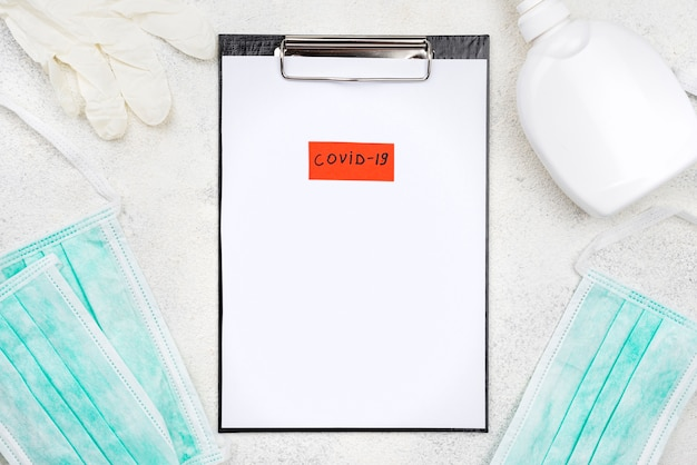 Composición de escritorio médico con etiqueta covid-19 en el portapapeles