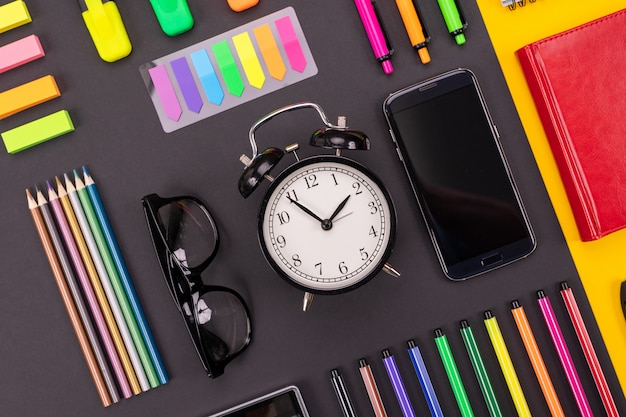 Composición de escritorio de negocios con reloj despertador, teléfono inteligente, cuaderno, pegatinas