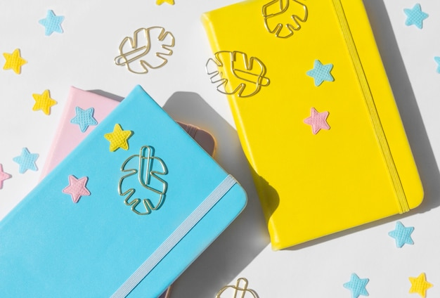 Composición de escritorio plana femenina con libretas de color rosa, amarillo y azul, estrellas y clips de oro monstera