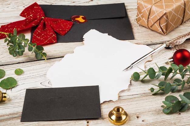 Composición de estilo vintage con papel desgastado y pluma sobre mesa de madera de cerca