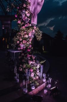 Composición exterior hecha de rosas y vegetación con velas iluminadas en la noche.