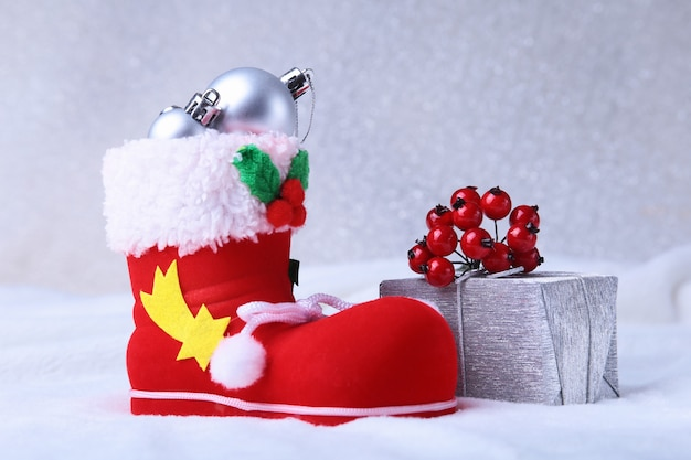 Composición feliz navidad zapato de santa claus con cajas de regalo sobre plumas ondulantes con nieve y copos de nieve. felices vacaciones.