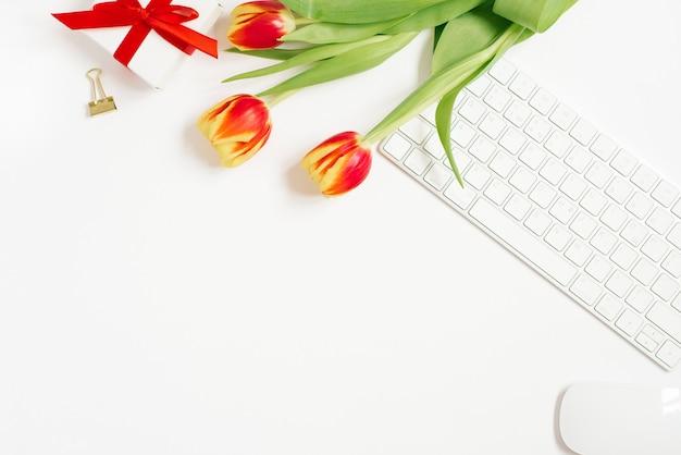 Composición femenina del espacio de trabajo de las mujeres, regalos. regalo con cinta roja y ramo de tulipanes, teclado. vista plana y superior