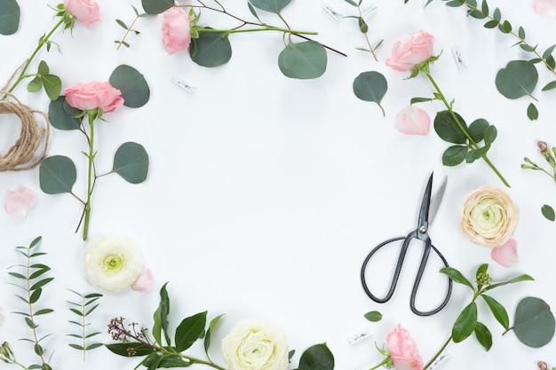 Composición festiva con flores, cuaderno, regalos, tijeras, cintas, hojas sobre un fondo blanco, vista superior y endecha plana, marco floral