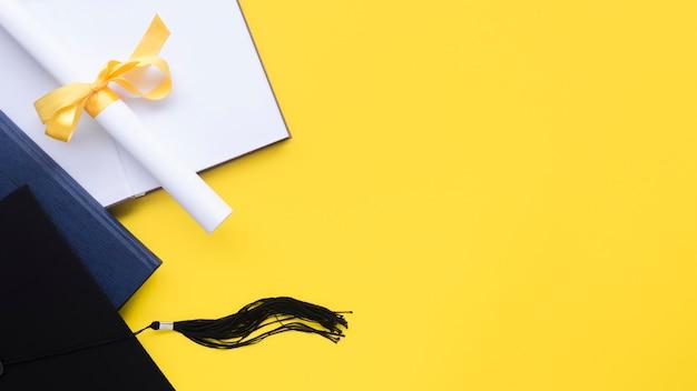 Composición festiva de graduación sobre fondo amarillo con espacio de copia
