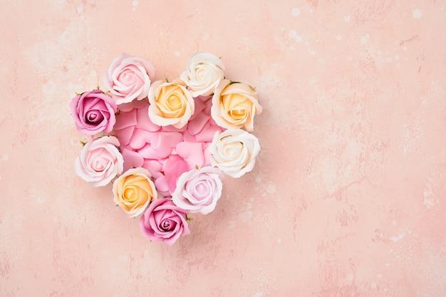 Composición festiva con hermosas flores de rosas delicadas en caja redonda rosa sobre mesa rosa claro. endecha plana, copie el espacio.