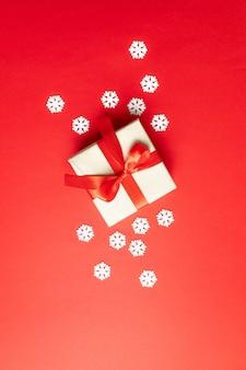 Composición festiva de navidad con copos de nieve y caja de regalo en rojo. invierno endecha plana, vista superior, copyspace