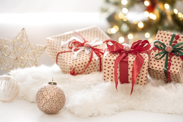Composición festiva de navidad con tres cajas de regalo sobre fondo bokeh de cerca.