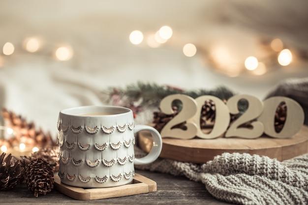 Composición festiva con taza blanca y guirnalda ligera.