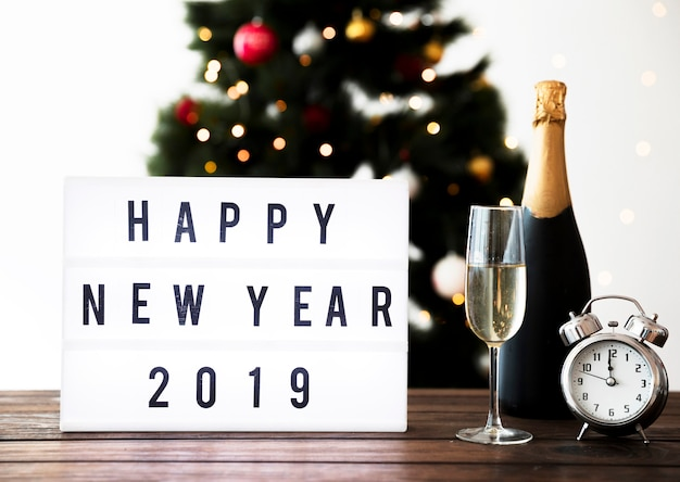 Composición de fin de año con champagne y reloj y felicitaciones.