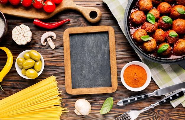 Composición flat lay de comida italiana con plantilla de pizarra