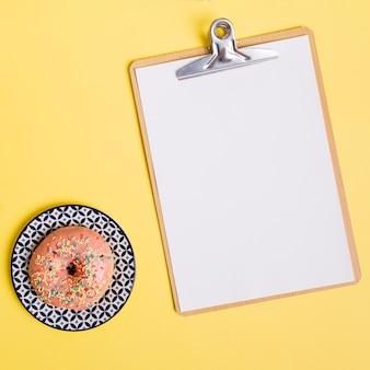 Composición flat lay de donuts con portapapeles