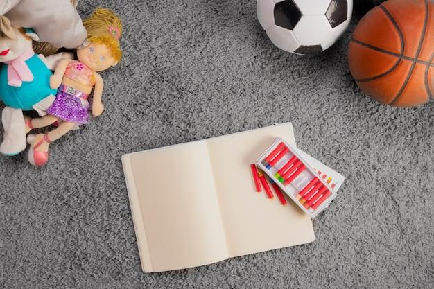 Composición flat lay de juguetes y plantilla de libro abierto