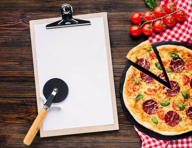 Composición flat lay de pizza con plantilla de portapapeles