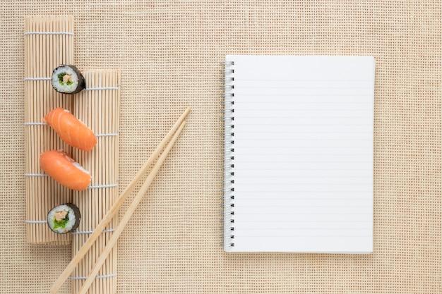Composición flat lay de sushi con plantilla de libreta