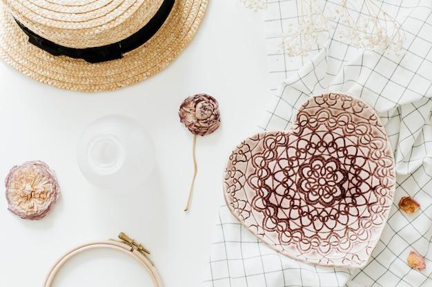 Composición flatlay con placa de estilo rosa corazón hecho a mano, flor color de rosa y sombrero de paja sobre superficie blanca. endecha plana, vista superior