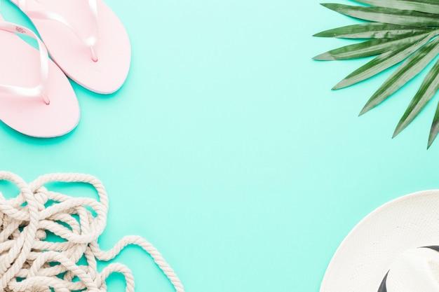 Composición de flip flops cuerda sombrero y hoja.