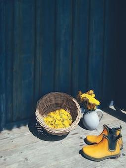 Composición floral con botas de jardín en azul y amarillo.