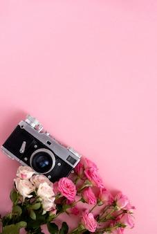 Composición floral con una corona de rosas rosadas y cámara retro en rosa. día de san valentín